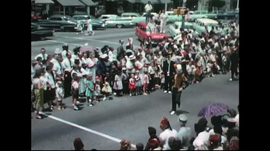 UNITED STATES: 1960s: musicians in marching band. People wave from car.