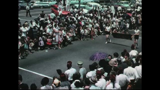 UNITED STATES: 1960s: girls carry banner. Marching band. Car in parade. Car pulls float.