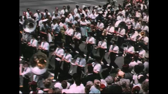 UNITED STATES: 1960s: marching band. Man dances to band. Vintage cars and floats. Horses in parade.