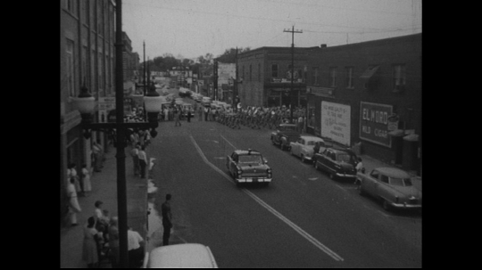 UNITED STATES: 1950s: band marches onto street.