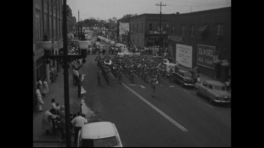 UNITED STATES: 1950s: band marches along street. Drum Major raises baton in time to music.
