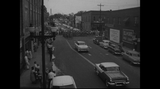 UNITED STATES: 1950s: cars drive through street. Marching band in procession. Band marks time.