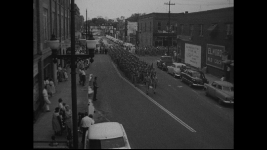 UNITED STATES: 1950s: people in uniform march along street.