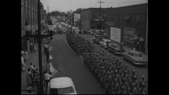 UNITED STATES: 1950s: people in uniform march along street. Flag bearers in parade.