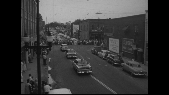 UNITED STATES: 1950s: cars in street parade. Band marches behind cars.