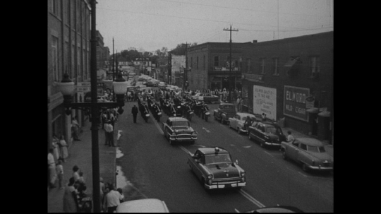 UNITED STATES: 1950s: cars in street parade. Band marches behind cars. Band marks time.