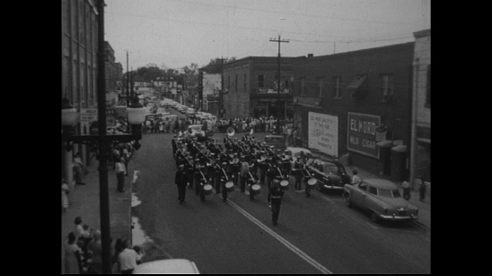 UNITED STATES: 1950s: marching band musicians perform in street.