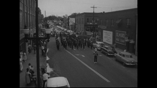 UNITED STATES: 1950s: drum major leads marching band along street
