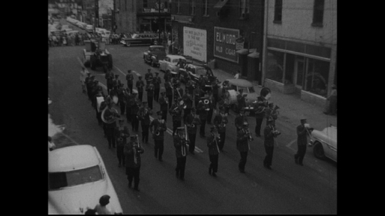 UNITED STATES: 1950s: drum major leads marching band along street. Vehicles and floats in parade.