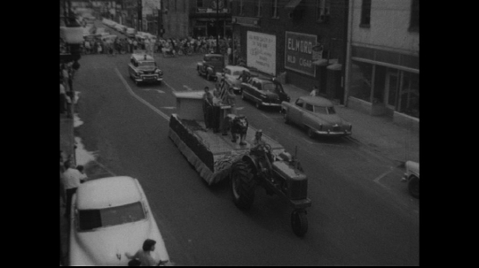 UNITED STATES: 1950s: tractor pulls parade float. Vehicles in parade.
