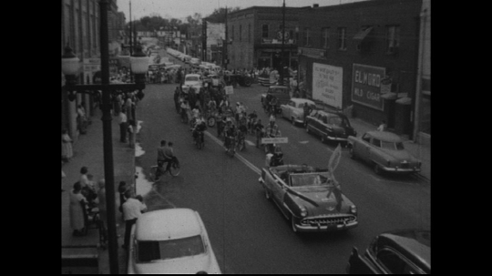 UNITED STATES: 1950s: vehicles in street parade. Girl walks with foal. Bikes in parade.