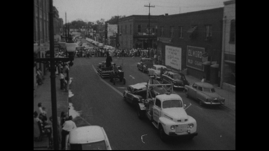 UNITED STATES: 1950s: smashed car pulled behind tow truck. Majorettes march in street.