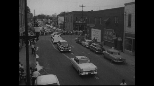 UNITED STATES: 1950s: vehicles drive along street in parade.