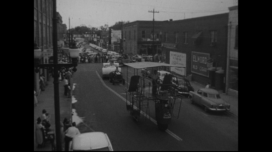 UNITED STATES: 1950s: vehicles drive along street in parade. Tractor is street parade. People on float.