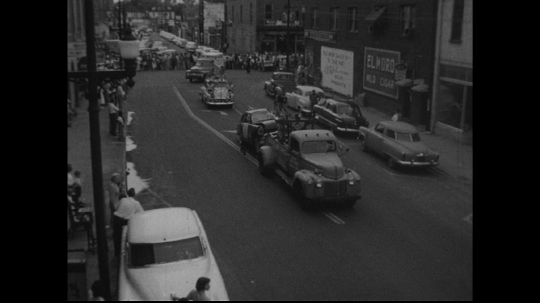 UNITED STATES: 1950s: tow truck pulls car through street.  Vehicles in parade