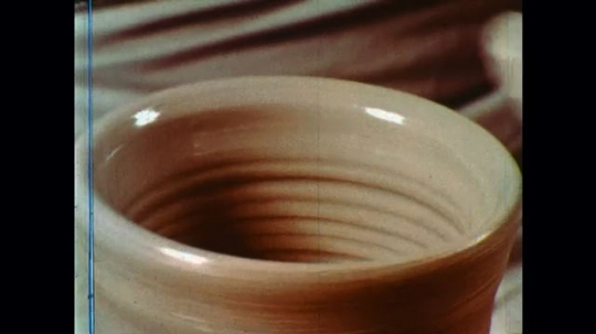 UNITED STATES: 1960s: hands shape pot of wheel.  Texture on clay.