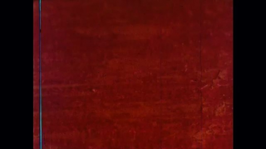 UNITED STATES: 1960s: brush dabs orange paint on red surface.