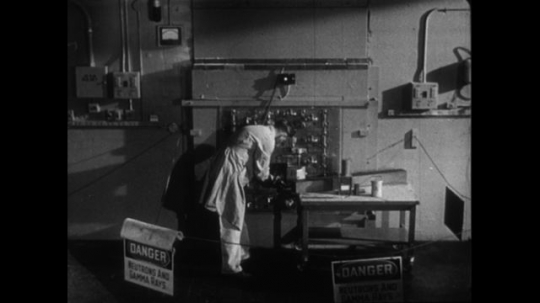 UNITED STATES 1950s: A scientist in a cancer research hospital places blocks of atomic material into a furnace.