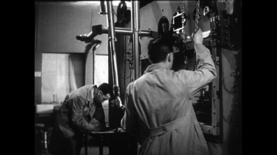UNITED STATES 1950s: Two scientists operate a robotic arm, via remote control, to work with atomic materials in a testing chamber.