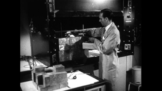 UNITED STATES 1950s: A lab technician uses a radiation testing machine to read the emissions from a stack of gallium blocks.