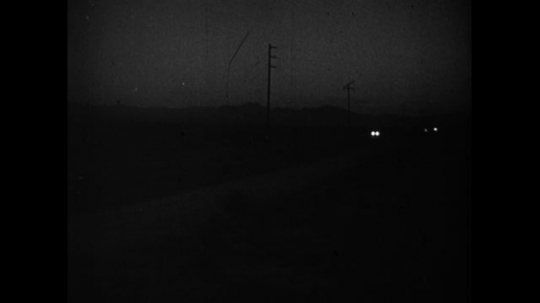UNITED STATES 1950s: A man and woman drive through a dark road until they are stopped at a post by a police officer flashing a light.