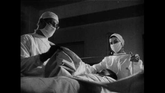 UNITED STATES 1950s: A medical staff prepares to perform surgery on a cancer patient after finding the location of his tumor.