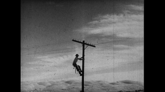 UNITED STATES 1950s: A man climbs up a telephone pole as manufacturing plants emit smoke.