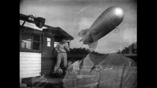 UNITED STATES 1950s: A balloon floats in the air next to a house as a man walks on a sidewalk in front of an institutional building.