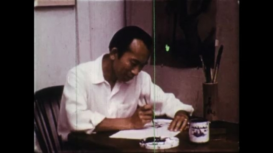 UNITED STATES: 1950s: man paints at table. Man dips brush in ink.