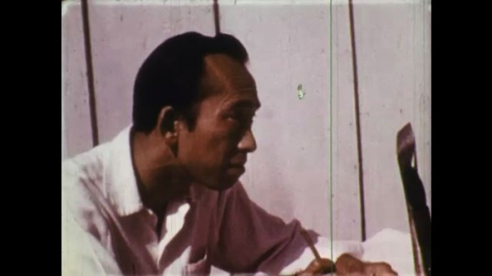 UNITED STATES: 1950s: side profile of man's face. Man paints at table. Hand paints lines on paper