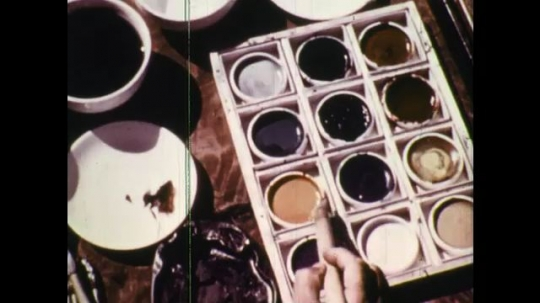 UNITED STATES: 1950s: hand dips brush into paint. Man paints fish on paper.