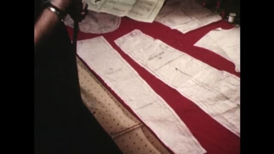 UNITED STATES: 1940s: lady moves pattern on material. Lady pins sheet to material.