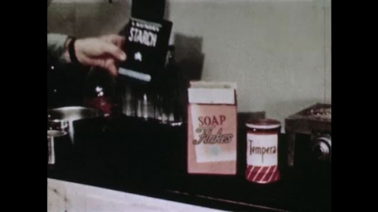 UNITED STATES: 1940s: hand puts starch and soap boxes on counter. Hand measures ingredients into bowl. Hand mixes powders.