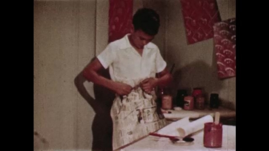 UNITED STATES: 1940s: boy puts on apron. Girl prepares paper. Boy flattens surface