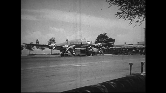 UNITED STATES 1950s : Long shot of an airplane on the runway, a man crouches on the wing as he fills the plane