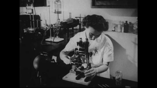 UNITED STATES 1940s-1950s : Female scientists conduct research using a microscope, a retro instrument panel/microphone, and test tubes.
