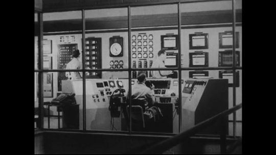UNITED STATES 1940s-1950s : Three scientists in a nuclear laboratory control room.  One scientist accepts a phone call while two others read the displays on panels.