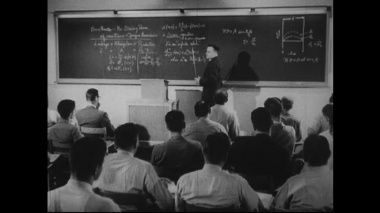 UNITED STATES 1940s-1950s : A professor lectures at the head of a classroom, filled with young men.  A young woman enters data onto punch cards using a computer.