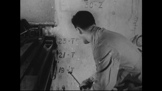 UNITED STATES 1940s-1950s : A scientist drops canister of radioactive material into a heavy lead container and carries it away from a nuclear pile.