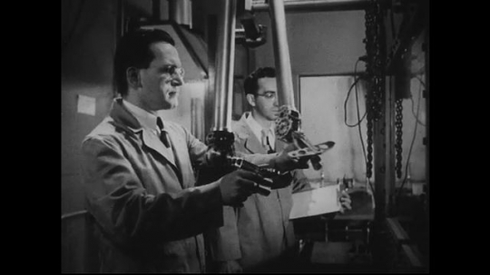 UNITED STATES 1940s-1950s : A scientist in a laboratory uses a remote control device to operate machine arms to work with radioactive material behind a glass window.