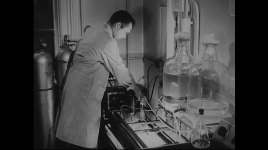 UNITED STATES 1940s-1950s : Flasks with a solution inside being shaken by a mechanical device, a scientist inspects them eventually