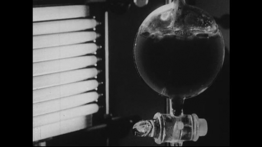 UNITED STATES 1940s-1950s : Science experiment. A chemical solution bubbles in a lab flask exposed to radioactive rods.