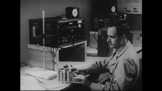 UNITED STATES 1940s-1950s : A scientist experiments with sample cylinders, using a control box with lots of knobs.