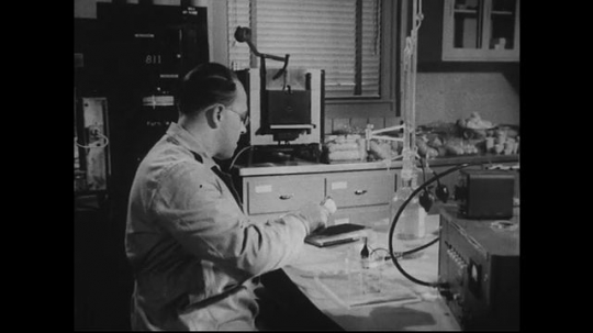 UNITED STATES 1940s-1950s : A scientist experiments with beakers, using equipment with lots of knobs.