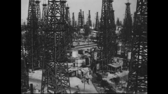 UNITED STATES 1940s-1950s : Shots of oil rigs. Pan across land filled with oil derricks.