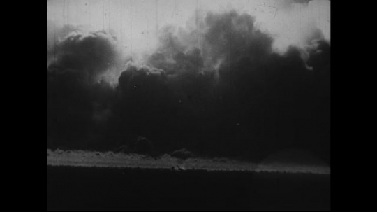 JAPAN 1940s: A bomb explodes on the ground causing smoke to rise and debris to fall.