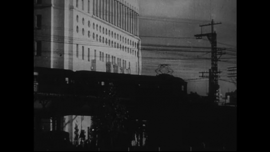 JAPAN 1940s: A train passes by a building in a city.