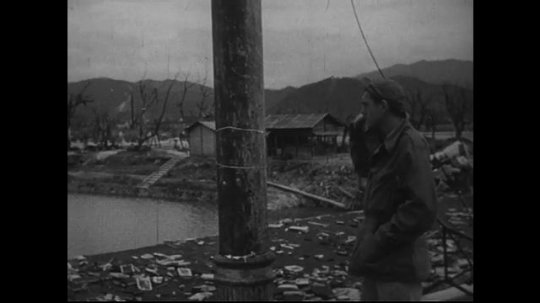 JAPAN 1940s: Damage evident on a bridge post and a building nearby.