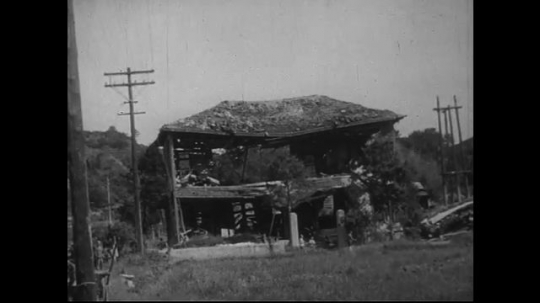 JAPAN 1940s: A house near the zero point leans sideways as restoration is under way.