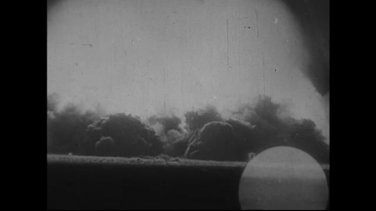 JAPAN 1940s: An atomic bomb is dropped into the ground and creates an explosion strong enough to form mushroom clouds.